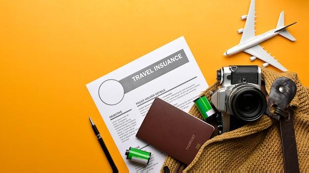 Escena de maqueta creativa, vista superior de la bolsa de viaje con cámara, pasaporte, formulario de seguro de viaje y artículos de viaje