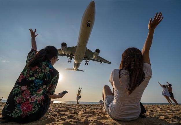 Escena de mujer de dos viajeros que muestra la mano y funning con aterrizaje de avión
