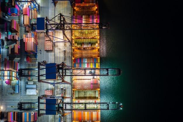 Escena nocturna carga y descarga de portacontenedores en el puerto de aguas profundas vista aérea del servicio comercial y la industria de carga logística de importación y exportación de transporte de carga por buque portacontenedores en mar abierto