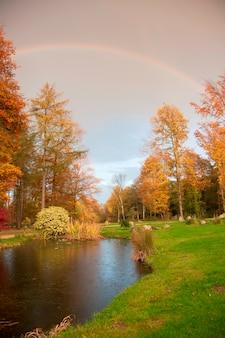 Escena de otoño con río y arco iris