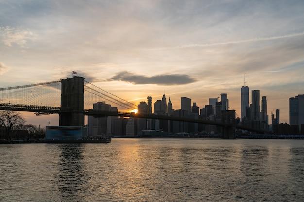 Escena del paisaje urbano de nueva york con el puente de brooklyn sobre el río east en el atardecer, horizonte del centro de estados unidos