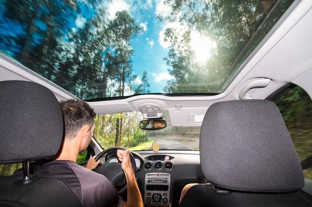 Escena que muestra a un hombre conduciendo un coche y la naturaleza.