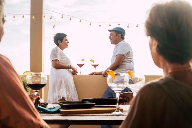 Escena romántica y amor con una pareja caucásica de mediana edad en el fondo hablando y permanecer juntos en la relación después de una cena con amigos.