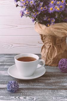 Escena romántica con una taza de té, flores de color lila en un jarrón sobre una mesa de madera gris