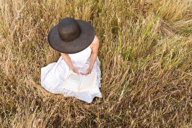 Escena romántica de la vista superior de ensueño de una mujer irreconocible sentada en un campo de trigo ellow grass