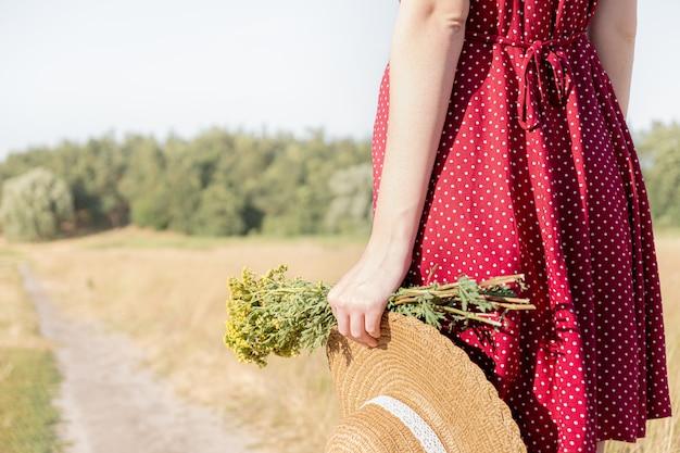 Escena rural: mujer con vestido de lunares con sombrero de granjero y ramo en la mano, vista de primer plano