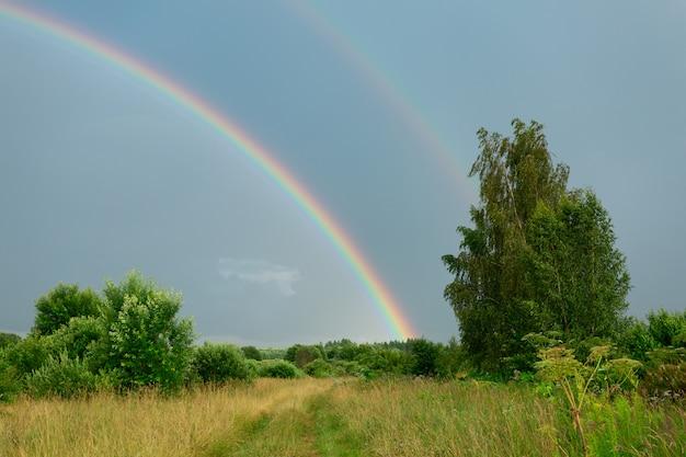 Escena rural con la naturaleza después de la lluvia con doble arco iris en el cielo oscuro.