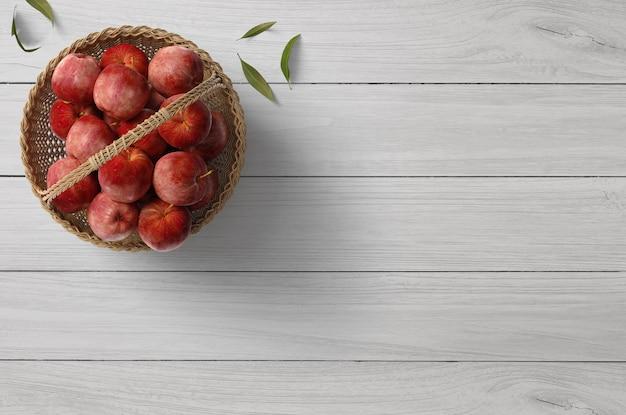 Escena simple de una mesa de madera clara con una cesta de manzanas rojas frescas y hojas verdes