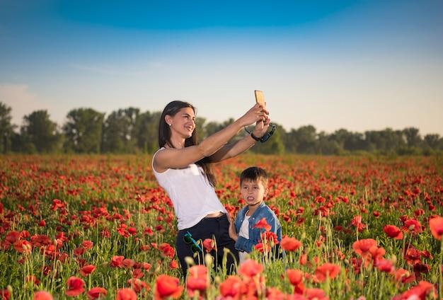 Escena de verano de feliz madre e hijo tomando selfie con smartphone en el campo de amapolas. día soleado de verano