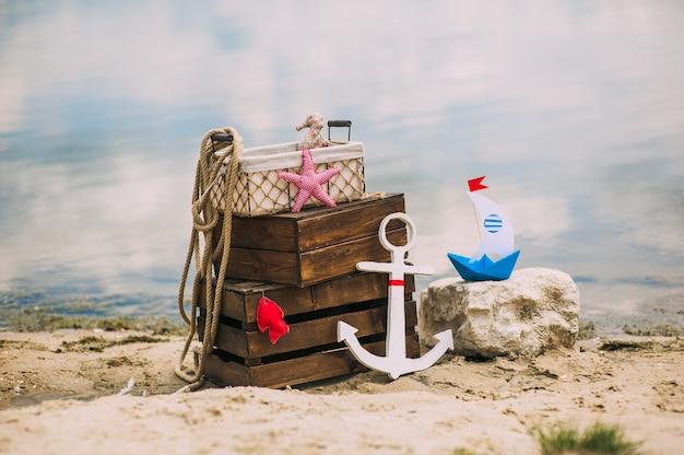 Escenografía y detalles en estilo náutico en la playa de arena. temas marinos. cajas de madera, ancla, barco, piezas de fábrica y cuerda de mar