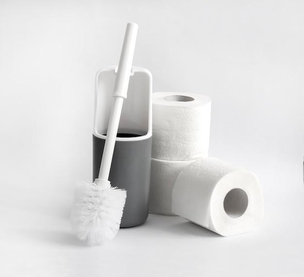 Escobilla de baño de plástico blanco y gris y rollo de papel higiénico sobre fondo blanco.