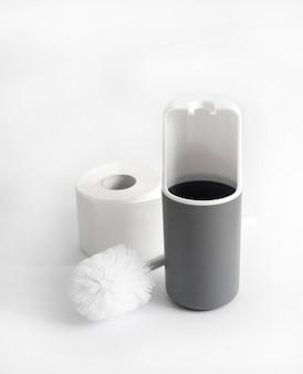 Escobilla de baño de plástico blanco y gris y rollo de papel higiénico sobre superficie blanca