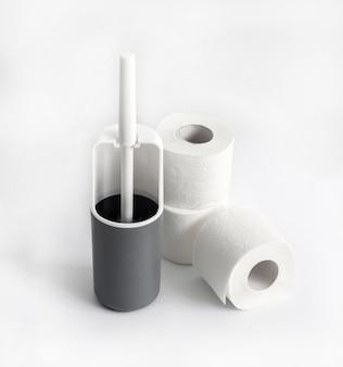 Escobilla de baño de plástico blanco y gris y rollos de papel higiénico sobre superficie blanca