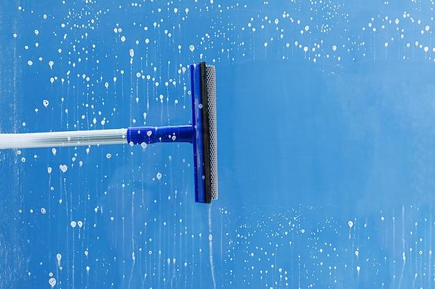 La escobilla de goma limpia la ventana. despeja una franja de ventana jabonosa. concepto de servicio de limpieza.