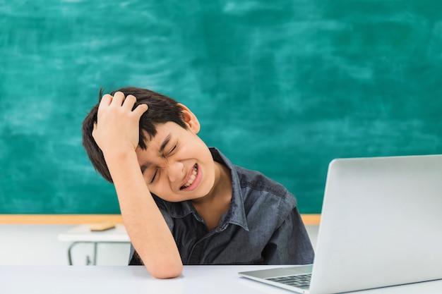 Escolar confuso asiático que usa el ordenador portátil en tablero negro