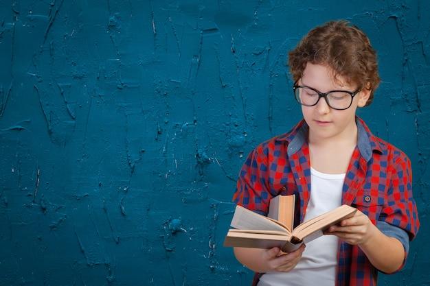 Escolar elemental lindo que sostiene el libro