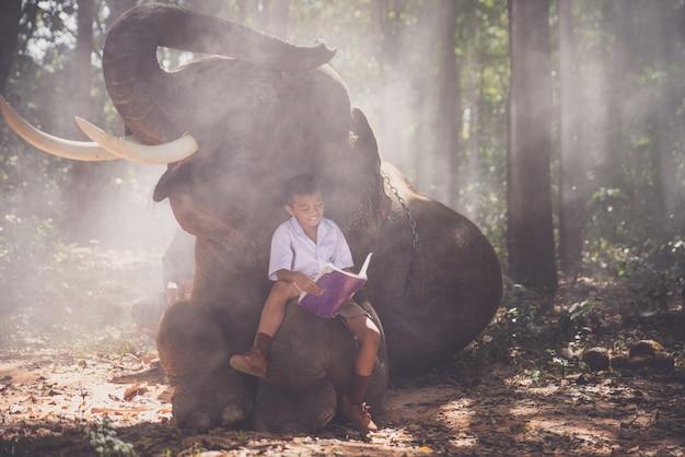 Escolar jugando en la jungla con su amigo elefante