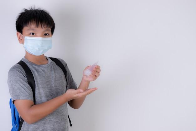 Escolar con mascarilla y aplicar desinfectante para manos. reabrir la escuela después de la pandemia de covid-19.