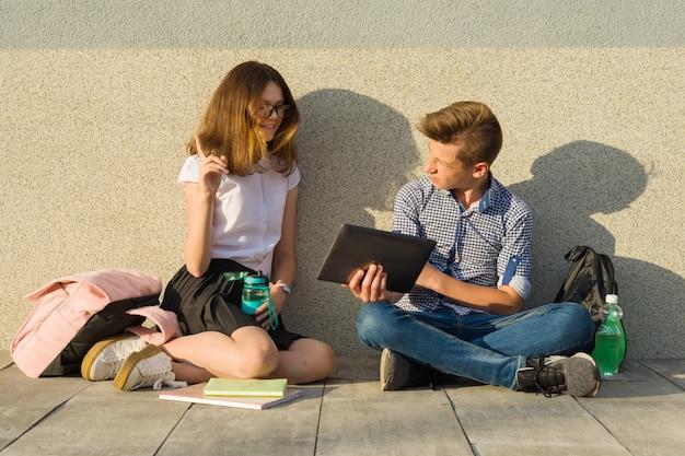 Los escolares los adolescentes miran la tableta