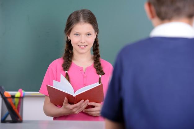 Los escolares están mirando y sonriendo.