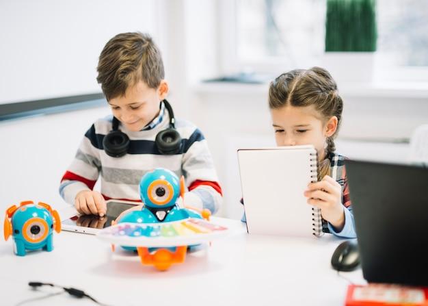 Escolares ocupados escribiendo notas y usando tableta digital en la clase.