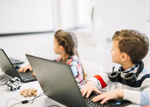 Escolares sentados con laptop mirando pizarra