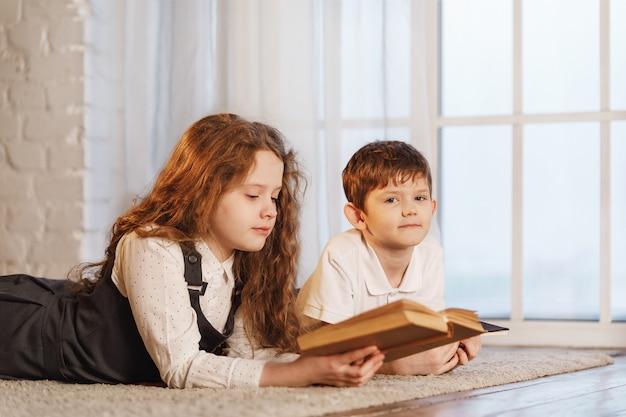 Escolares soñando y leyendo el libro en casa.