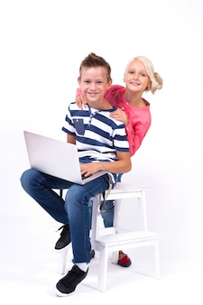 Los escolares sonrientes aprenden con la computadora portátil