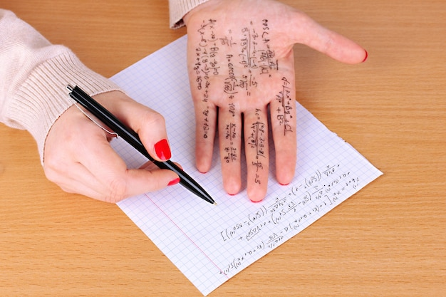 Escriba la hoja de trucos en la mano en primer plano de la mesa de madera