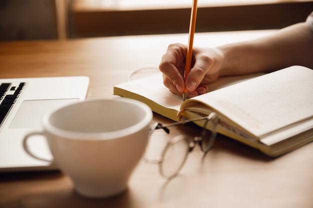 Escribiendo. cerca de manos femeninas caucásicas, trabajando en la oficina.
