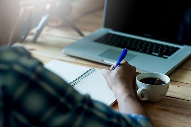 Escribiendo en el papel en el trabajo en la mesa por la mañana, ideas de negocios. hay espacio para copiar.