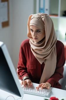 Escribiendo en el teclado. mujer musulmana de ojos oscuros escribiendo en el teclado mientras busca información