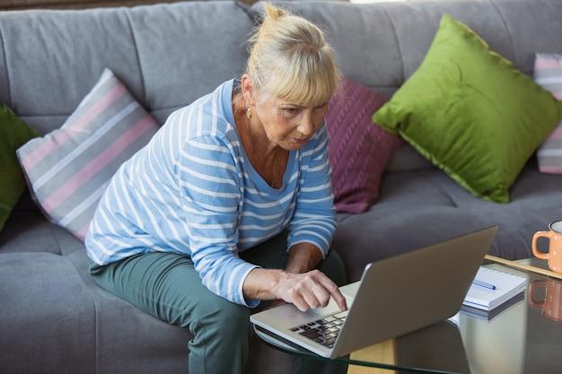 Escribiendo texto, mensaje. mujer mayor estudiando en casa, obteniendo cursos en línea, autodesarrollo. mujer caucásica que usa dispositivos modernos para divertirse, educarse, dedicar tiempo a un nuevo trabajo o pasatiempo.