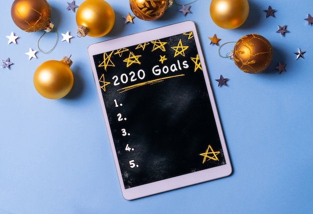 Escribir la lista de objetivos de año nuevo 2020 en una tableta sobre fondo azul con bolas doradas de navidad y estrellas plateadas.