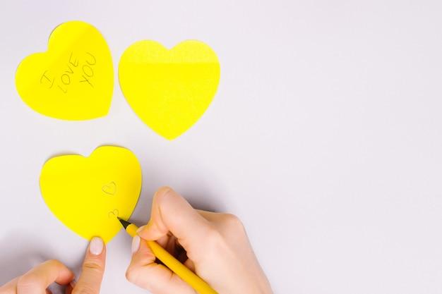 Escribir mensaje de amor a mano en corazones de nota iluminadores sobre fondo gris definitivo.