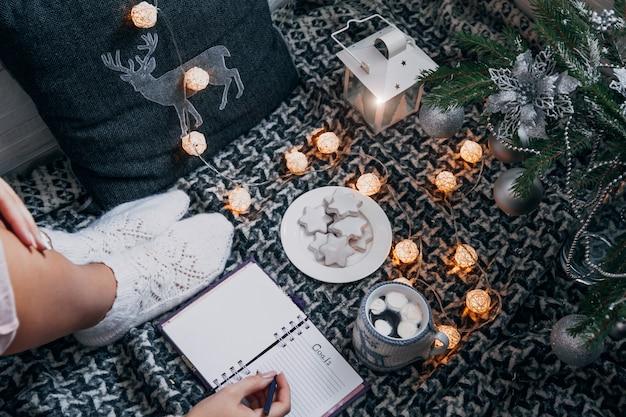 Escribir metas para el próximo año con una taza de chocolate debajo del árbol de navidad