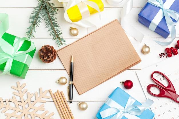 Escribir tarjetas de felicitación de navidad. bloc de notas abierto con bolígrafo sobre mesa de madera decorada