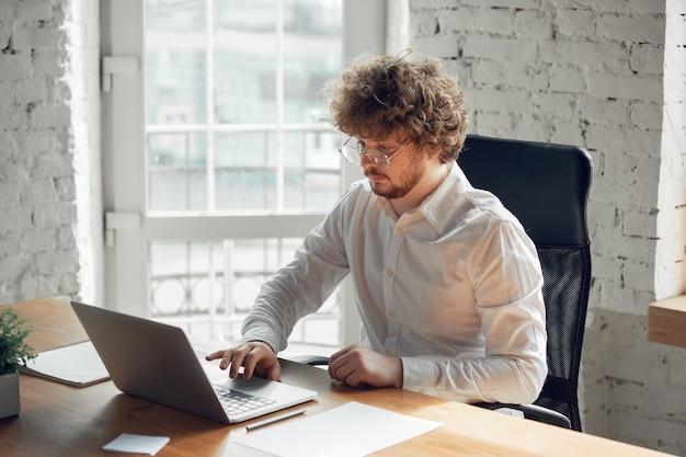Escribir texto, analizar, navegar. hombre joven caucásico en traje de negocios trabajando en oficina. joven empresaria, gerente haciendo tareas con teléfono inteligente, computadora portátil, tableta tiene conferencia en línea, estudiando.
