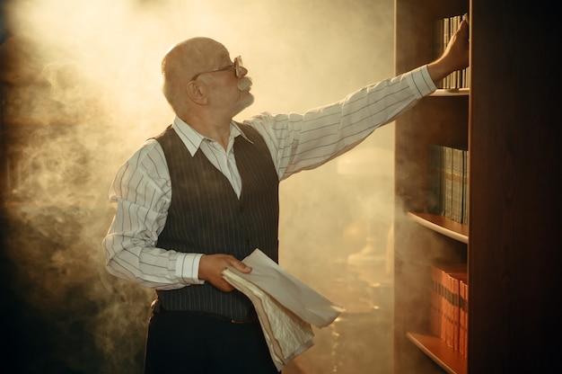 Escritor anciano con hojas de papel de pie en la estantería de la oficina en casa. anciano con gafas escribe novela literaria en la habitación con humo, inspiración