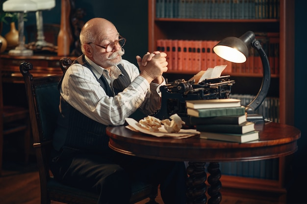 El escritor anciano piensa en la máquina de escribir vintage en la oficina en casa. anciano con gafas escribe novela literaria en la habitación con humo