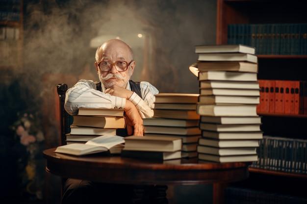 Escritor anciano sentado a la mesa con una pila de libros en la oficina en casa. anciano con gafas escribe novela literaria en la habitación con humo, inspiración