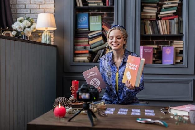 Escritor exitoso. agradable mujer rubia sosteniendo libros mientras habla de ellos a la cámara