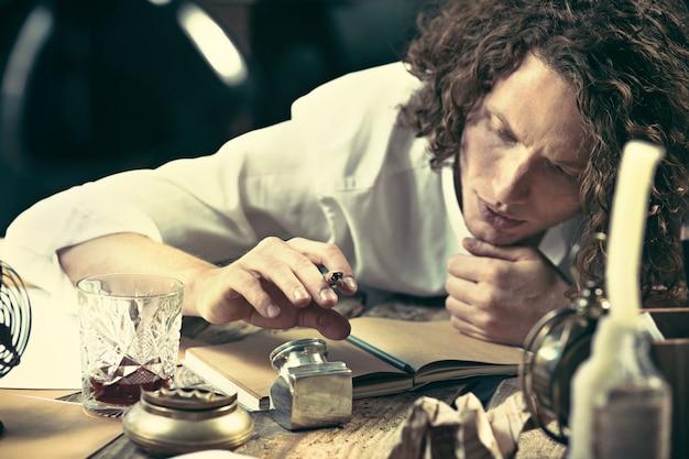 Escritor en el trabajo. apuesto joven escritor sentado en la mesa y escribiendo algo en su bloc de dibujo en casa