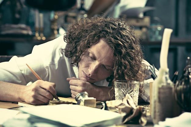 Escritor en el trabajo. apuesto joven escritor sentado en la mesa y escribiendo algo en su bloc de dibujo