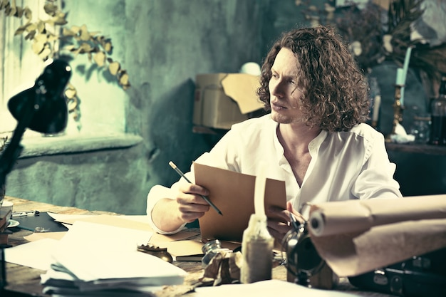 Escritor en el trabajo. joven escritor sentado a la mesa y escribiendo algo en su bloc de dibujo en casa