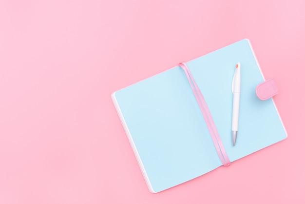 Escritorio de área de trabajo con diseño de suministros de oficina sobre fondo rosa pastel