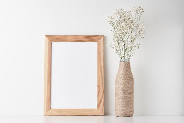 Escritorio de área de trabajo con marco vacío y flor en florero.