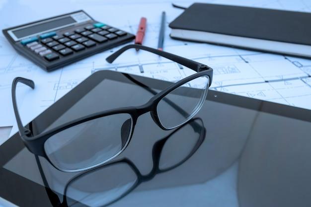 Escritorio de arquitecto con planos de construcción, tableta, gafas en el estudio de arquitecto