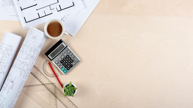 Escritorio de arquitecto con planos y espacio de copia