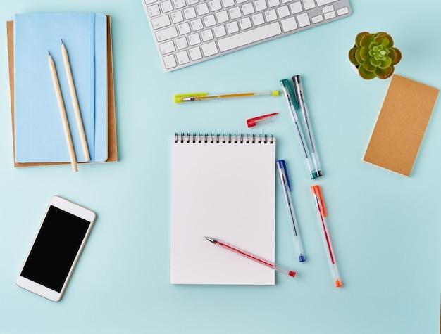 Escritorio azul moderno de la oficina de la vista superior con la libreta en blanco